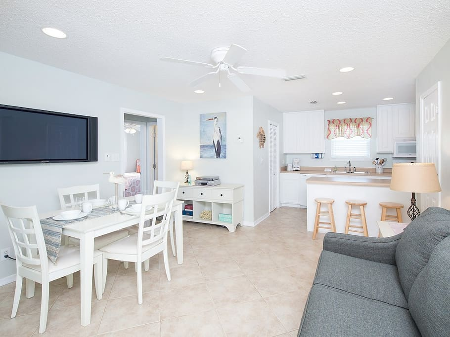 Sunny, open-concept living area with a flat-screen TV and dining for 4