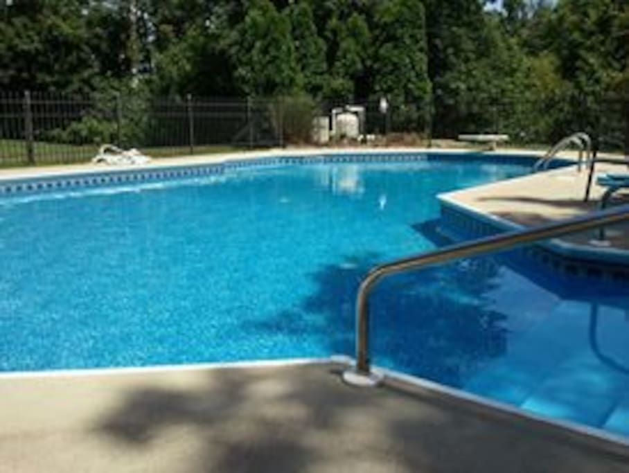 Large play pool with diving board,  basketball goal, volleyball net and couples bench in the deep end.