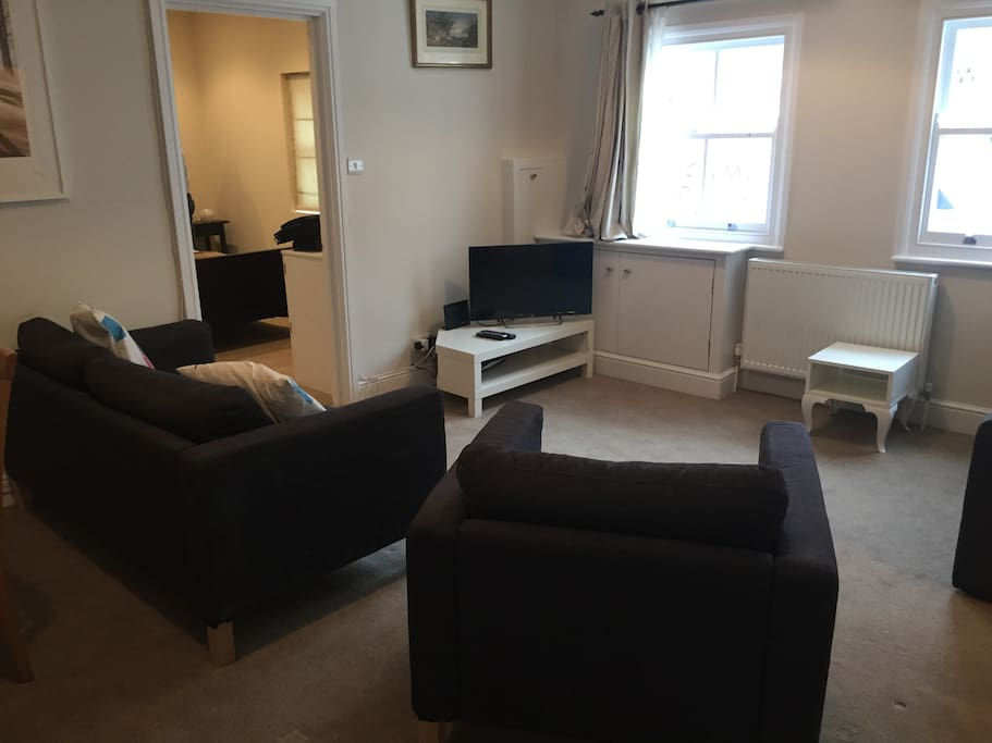 Sitting room area with sofa and armchair and TV