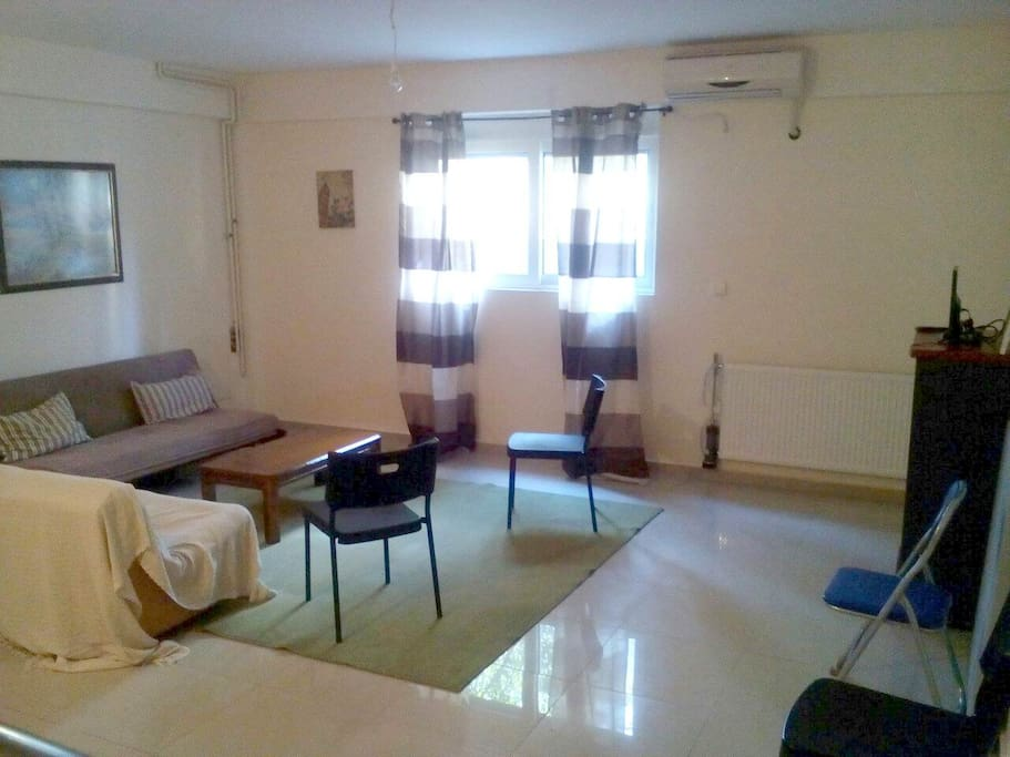A two room studio on the underground floor sunny and bright. One space has couches and 2 single beds with tv and bathroom.The second space has one double bed.