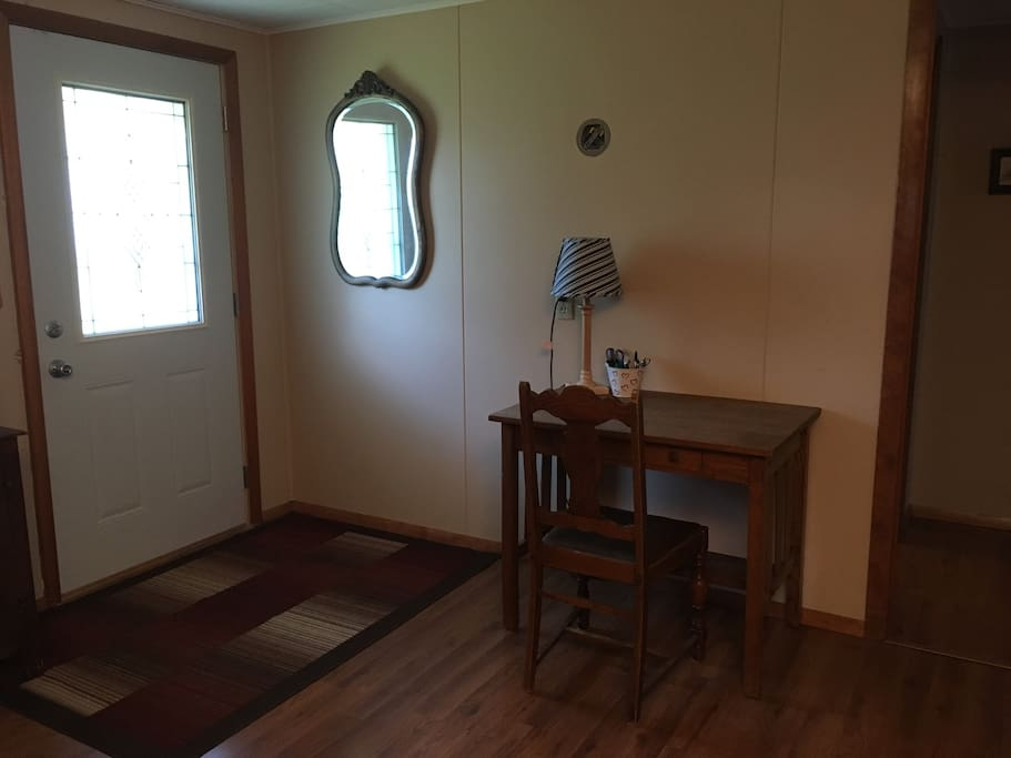 Front door leads into living room with desk.