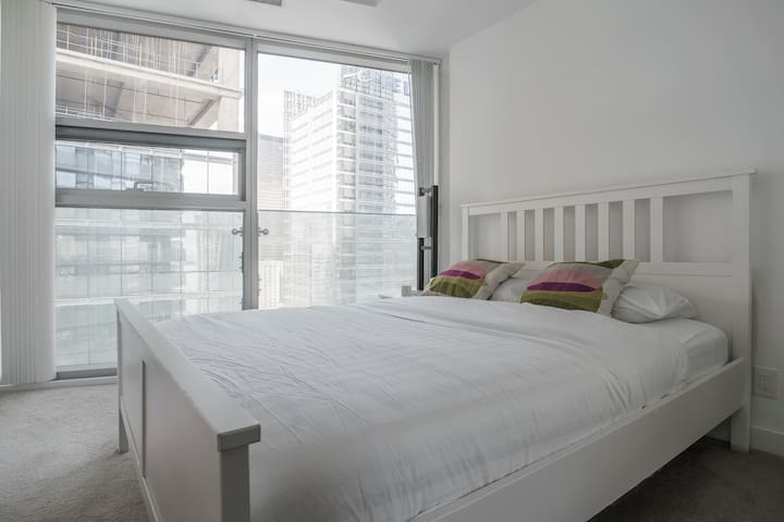 Bed room with full window to enjoy morning or night city lights .
