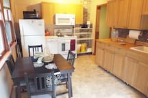 The kitchen is fully equipped with a stove, fridge, microwave, dishwasher, coffee maker, and other small appliances. You'll also find cookware, dishes, cutlery, and spices.