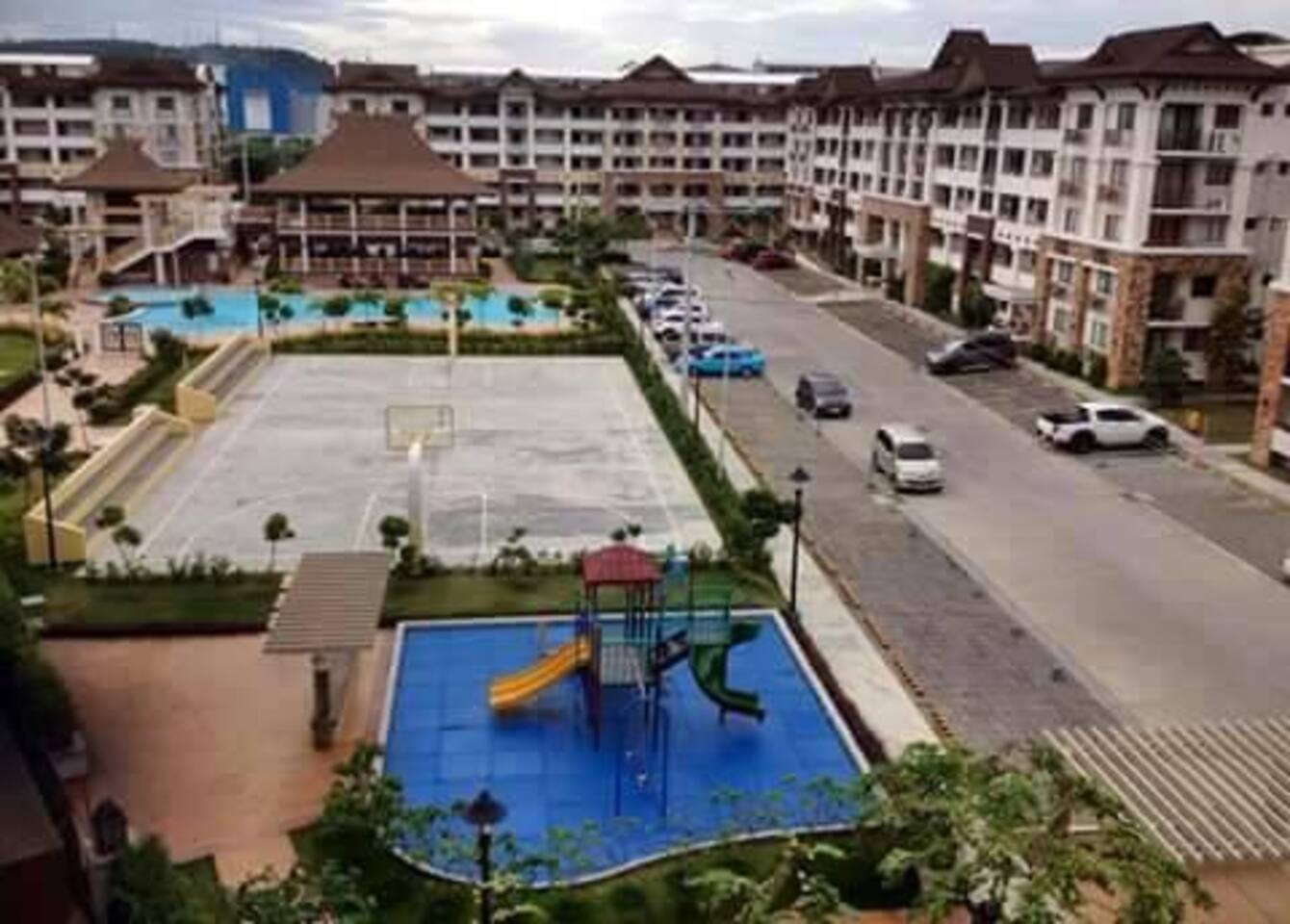 Our Clubhouse, Kiddie Pool, Adult Pool, Basketball Court and Kiddie Playground with Condo Buildings at the back ground.