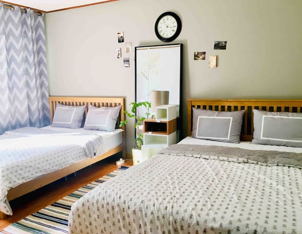 a Large room with clean bedding and a wide window of sunlight (2 queen beds, air conditioner)