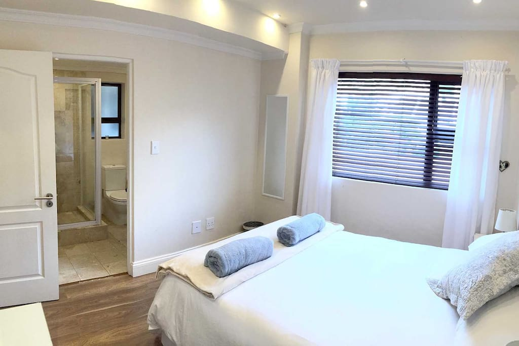 Separate bedroom with en-suite bathroom.  Bedroom includes a dressing table with a hairdryer and cupboards with shelving and hangers.