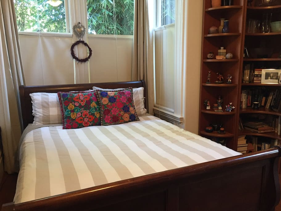 Queen size sleigh bed surrounded by books