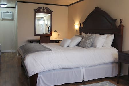 The Ledgestone room features a large king size bed, hardwood floors, wainscotted walls, plaster ceiling tiles, stone gas fireplace, cable TV, air conditioning, and a direct access to the garden level terrace.