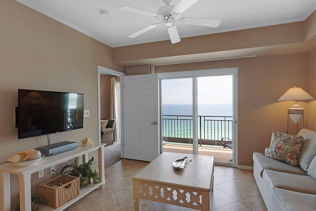 Large flat panel TV in living area with balcony access