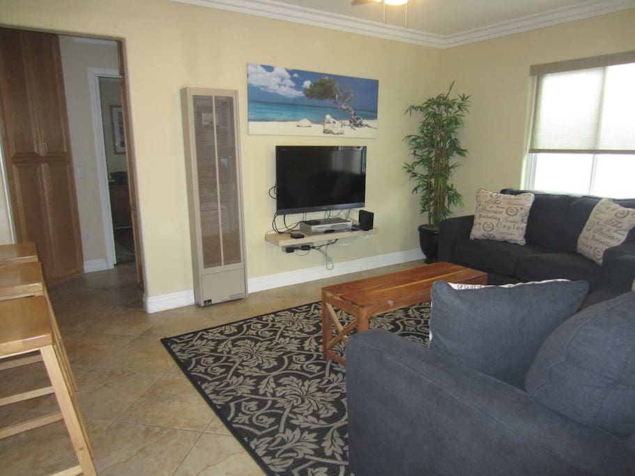 Living room off of kitchen w/TV and Apple device to access Netflix