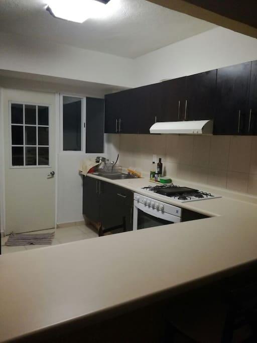 Amplia Cocina. Cuenta con refrigerador, estufa, barra de servicios.