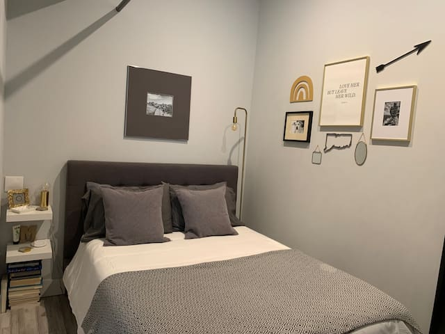 Bedroom has queen bed and is separated from hallway with a sliding door.