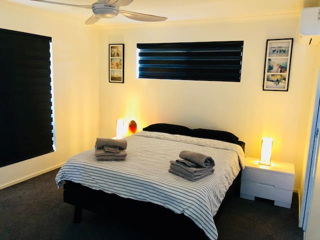 Main bedroom with floor to wall mirrors. Electric shutters, air conditioner and fan.