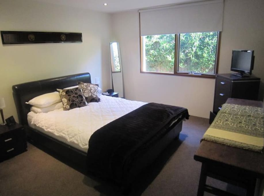 Bedroom 1 with built in robes and queen bed. TV with foxtel