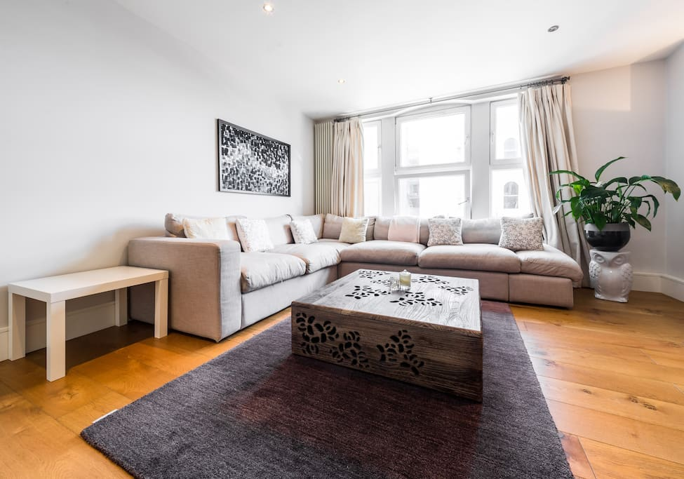 Spacious living area with lots of natural light and comfortable L shaped sofa