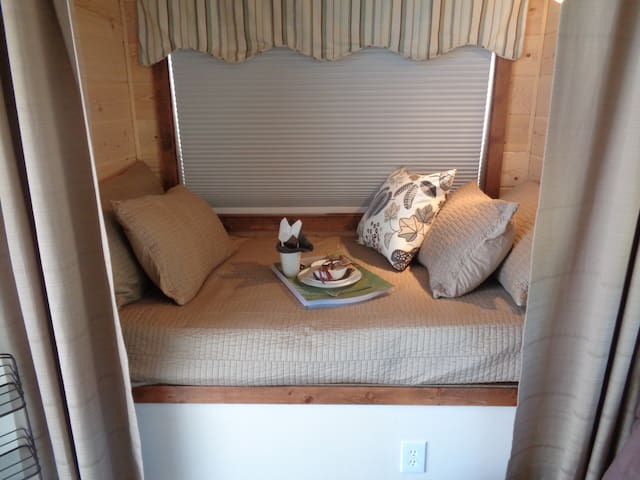 A cozy single daybed with blackout blinds and privacy curtains