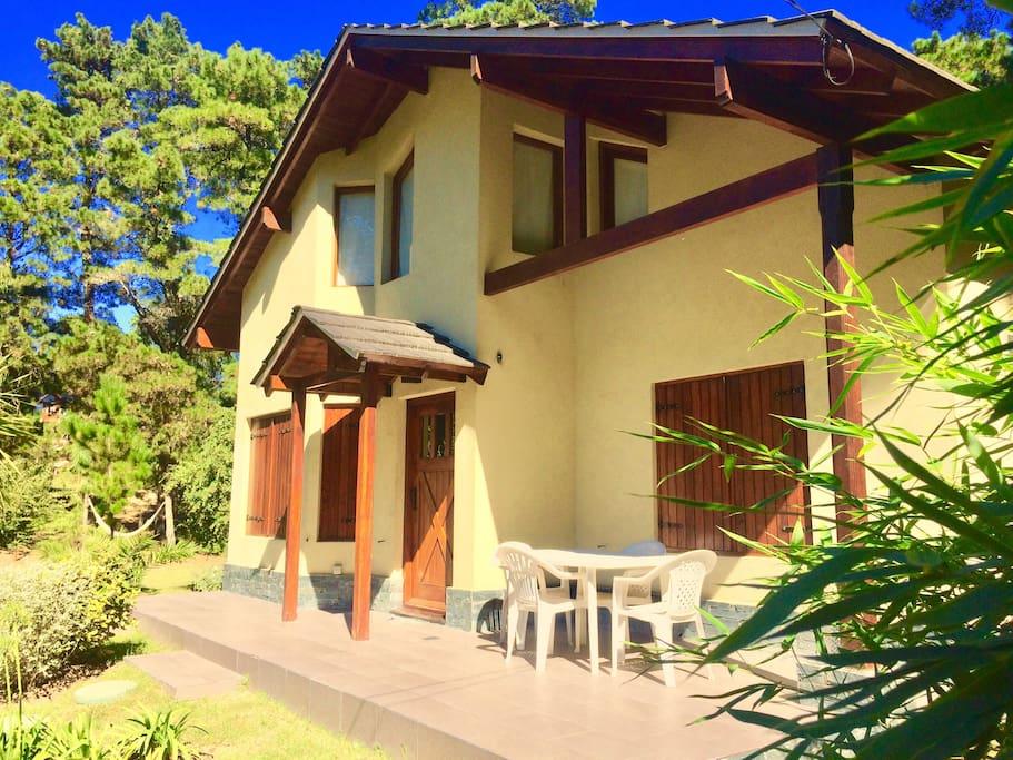 Deck en el frente de la casa con mesas y silla de exterior