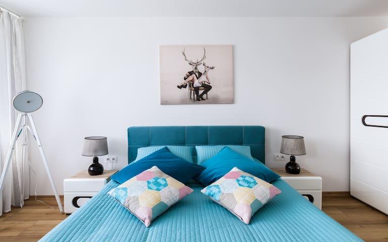 Sypialnia z bardzo dużym łóżkiem małżeńskim (KING BED), lampkami i klimatycznym obrazem