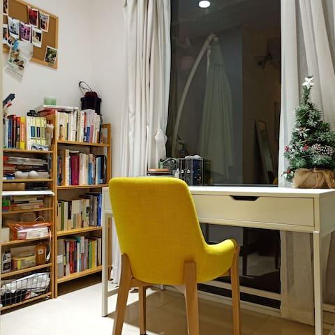 很适合独处的角落,大落地窗旁边就是书架