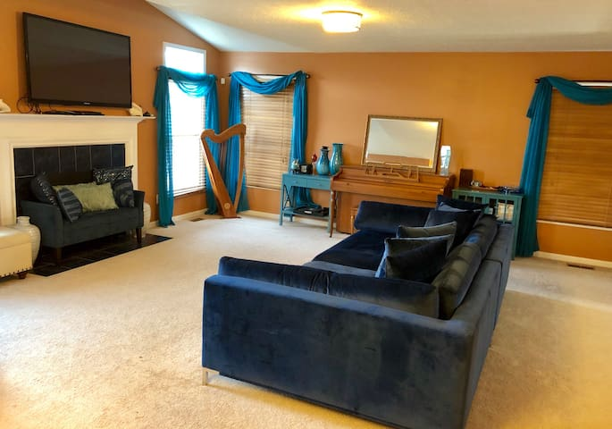 Family room with fireplace has a piano, comfortable sofa and plenty of space for family fun. Flat screen tv ensures great movie nights.