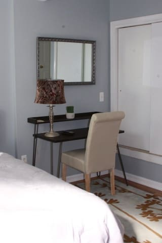 Work space within master bedroom. In the closet, you will find a luggage rack, shelves, hangers and laundry basket.