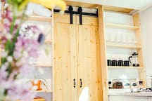 The sliding barn doors separate the large wet room with a large shower and a flushing toilet