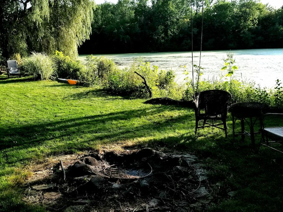 Fire Pit and furniture by the water and hammock under the willow tree!
