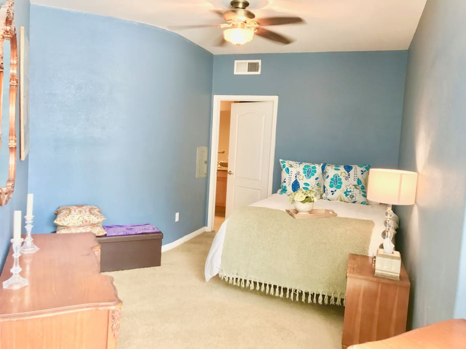 Spacious bedroom with queen bed, ceiling fan, dressers and air conditioning.
