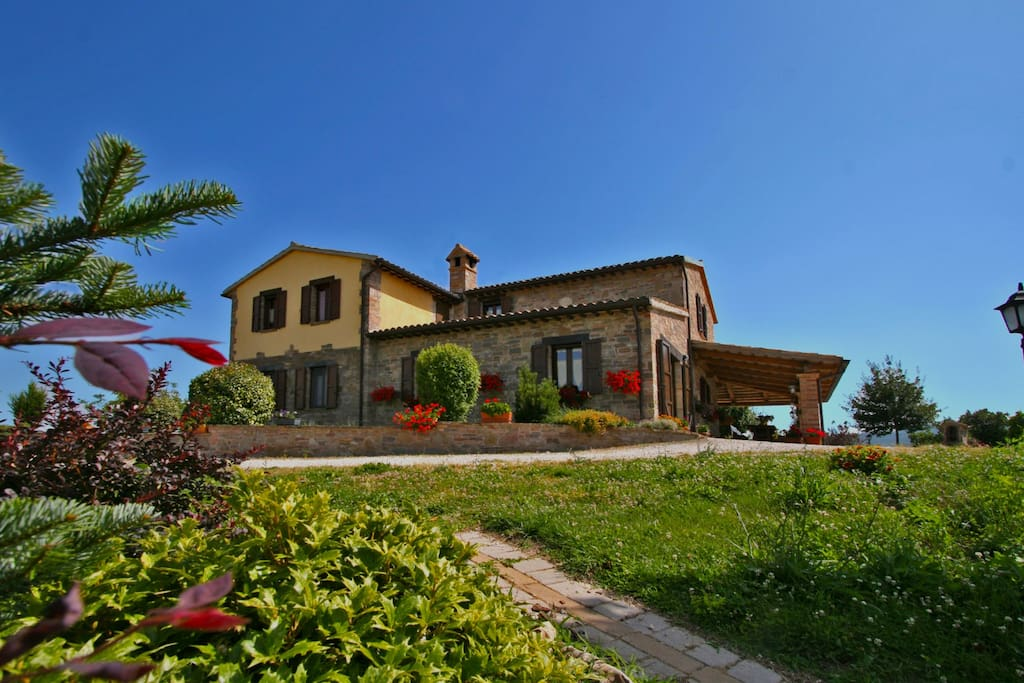 Large villa with porch and surrounding garden