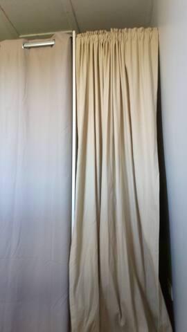 Votre lit est derrière les rideaux.