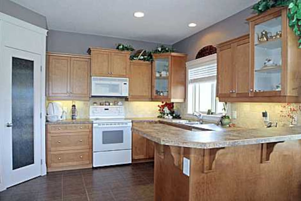 Gourmet kitchen with custom maple cabinets, breakfast bar, walk-in pantry and ceramic tile floors.