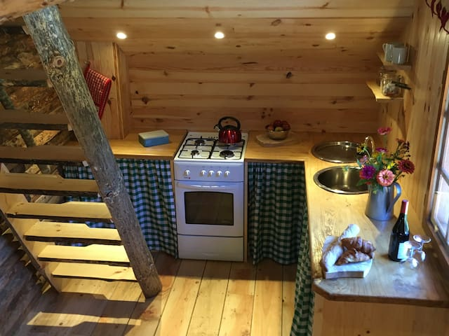 Kitchen area with gas cooker, sink with hot and cold running water. Stairs to sleeping mezzanine.