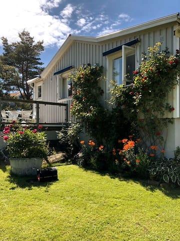 Havsnära ljust hus med stor trädgård.