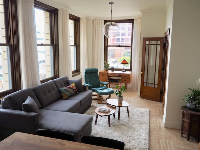 Living room with four huge 4' x 6.5' oak sash windows that fill the room with natural light.