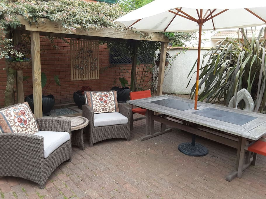 Relaxation in comfortable outdoor courtyard, with shade under umbrella and pergola, or morning sunny breakfast alfresco.