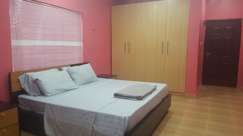 Pink room with king size bed and 1 twin bunk bed.