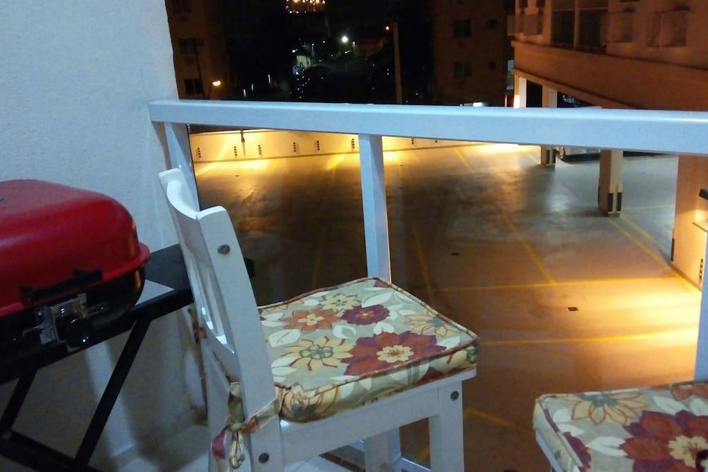 Varanda com churrasqueira e duas cadeiras altas