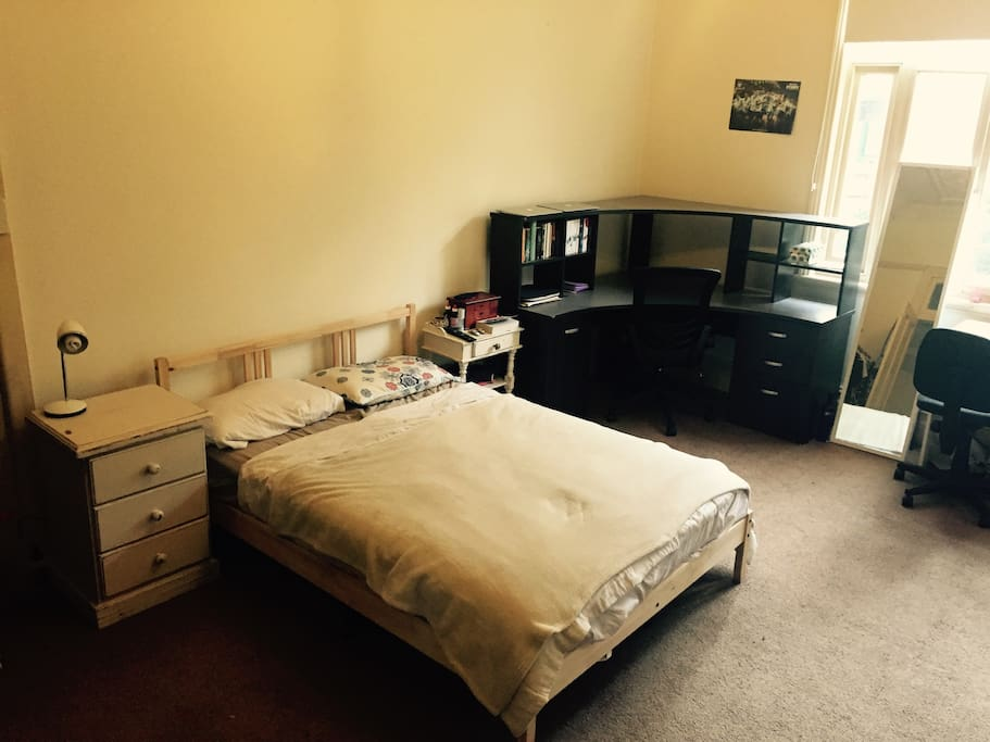 Spacious room with double bed, 1 large and 1 small desk, and storage space for clothes