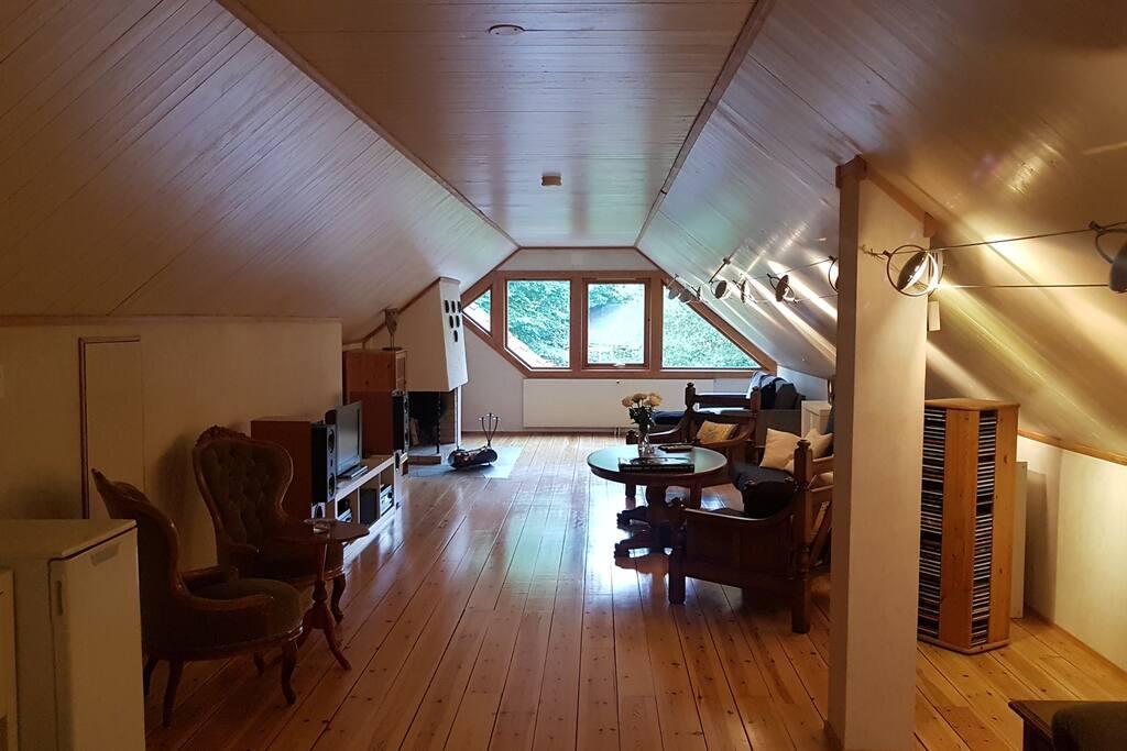 Romslig loftstue med stoler, bord og sofa. TV-benk med dekoder, forsterker, høyttalere og TV.