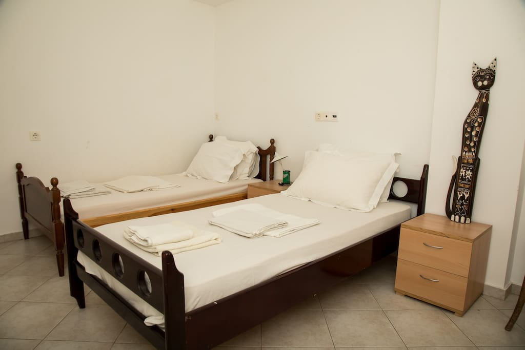 The furnished second bedroom is fitted with two single beds.