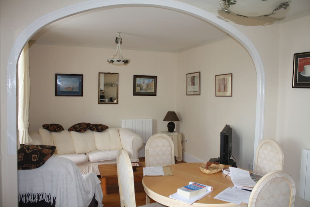 Spacious living and dining area with comfy chairs and TV