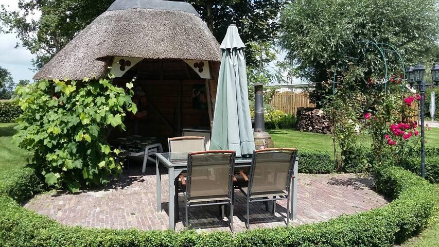 Het terras met stoelen en ligbed.