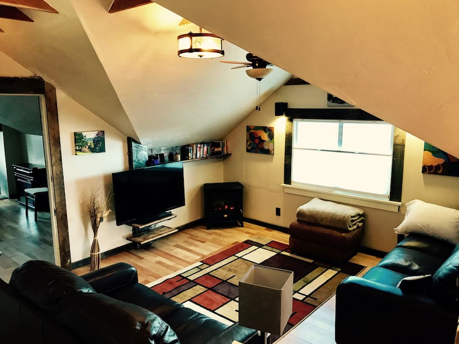 Custom metal/wood work supports floating TV, great lighting, comfy leather couches
