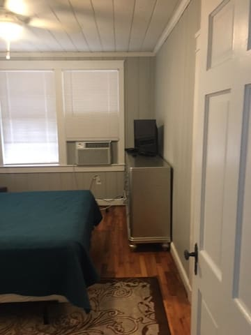 View of front bedroom with dresser, cable TV, window a/c unit, ceiling fan
