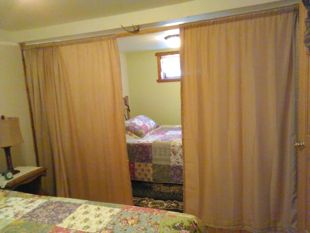 Bedroom with Privacy curtain separating 2 queen size beds...one with standard mattress the other with memory foam mattress.