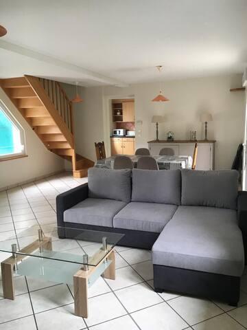 salon et salle à manger, cuisine indépendante au fond, escalier montant au chambre, canapé pouvant accueillir deux couchages