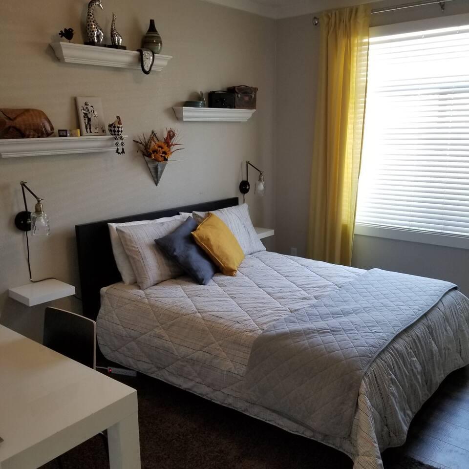 Bright and cheery room with TV, fridge, closet, desk