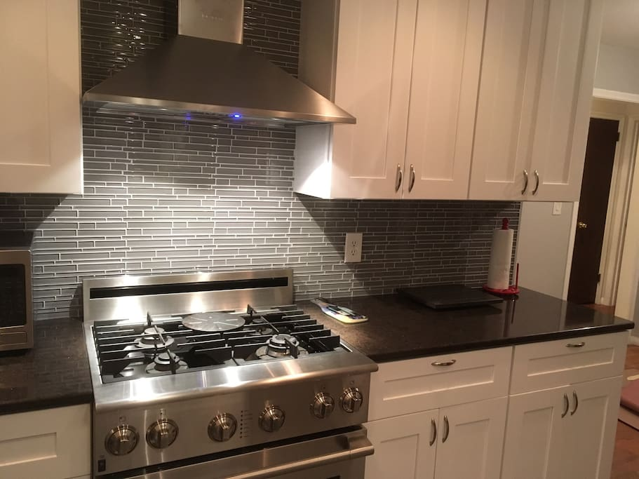 """Professional stove, hood and microwave. Part of the newly remodeled kitchen. """"This place was amazing! The pictures posted on Airbnb does it no justice. It's very well decorated. All of the appliances are high end. We really enjoyed the deck in the rear of the home. The beds are super comfortable. This will be my go to place during my next visit to Minneapolis. The host was very easy to communicate with and the book with the house rules and guide was very helpful. 5 stars all day."""""""