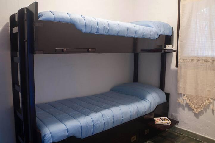 Camera con letto a castello in legno. Room with bunk bed in wood.
