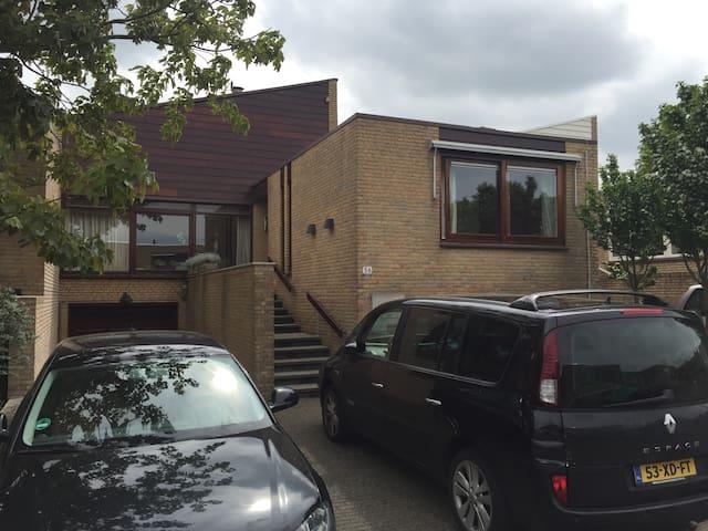 Het huis met voortuin, 2 parkeerplaatsen en deur naar garage te opnenen met afstandsbediening